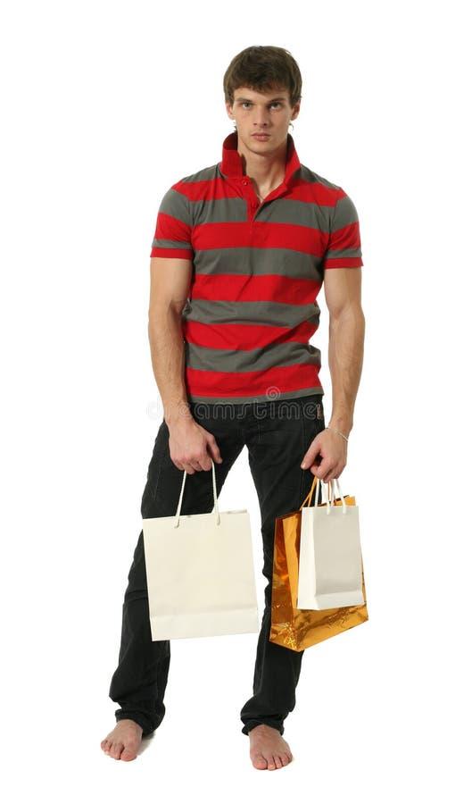 Junger reizvoller Mann mit Einkaufen-Beuteln stockbilder