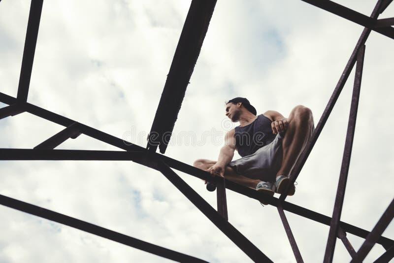 Junger riskanter Kerl, der auf die Oberseite des Baus des überstehenden Materials balanciert und sitzt lizenzfreie stockfotos