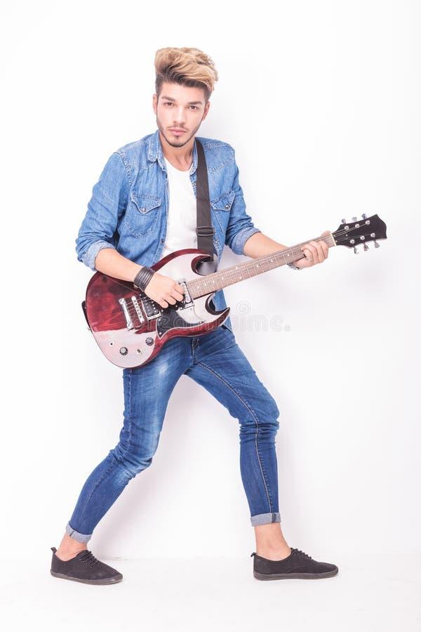 Junger Rocker, der seine rote E-Gitarre spielt stockfoto