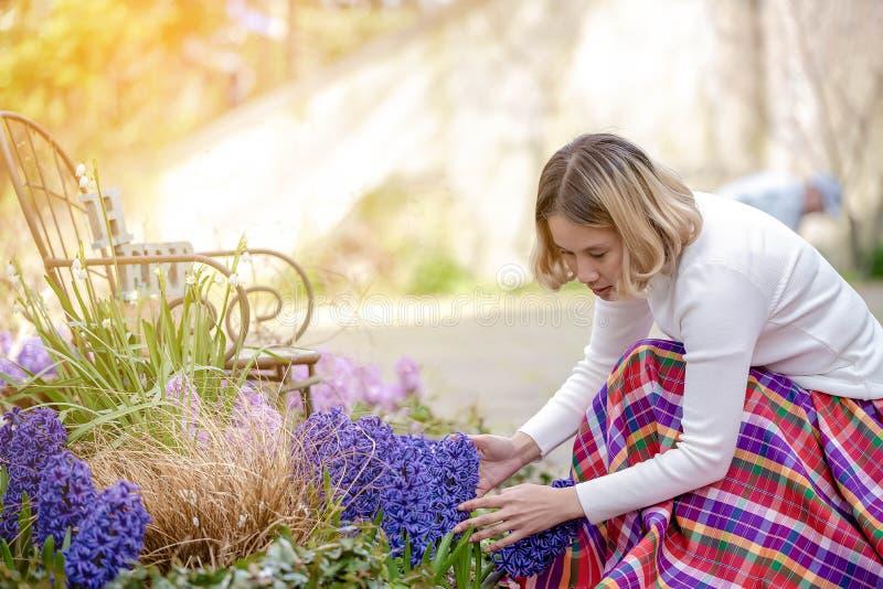 Junger schöner Asiatingärtner um ihrer Blume im Hinterhof sich kümmern lizenzfreie stockfotografie