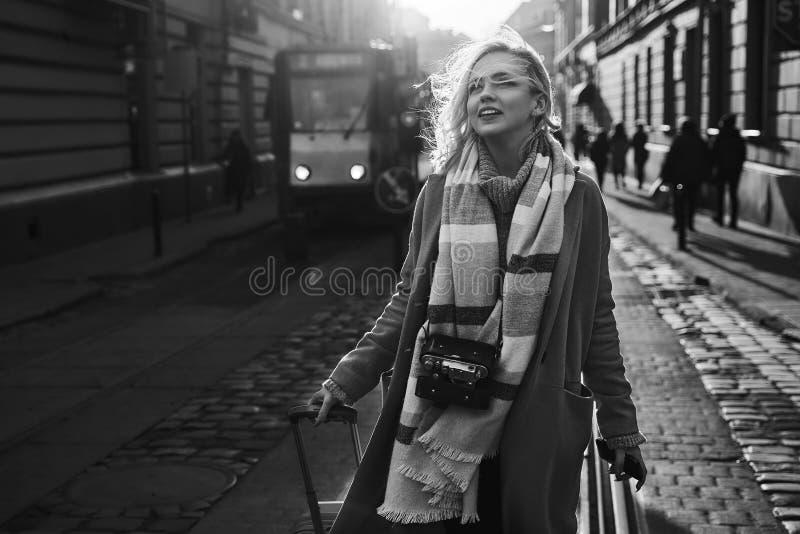 Junger schöner blonder Frauentourist mit einer fahrbaren Reisetaschen- und -weinlesefilmkamera kommt zur neuen Stadt an, um sie z lizenzfreie stockfotografie