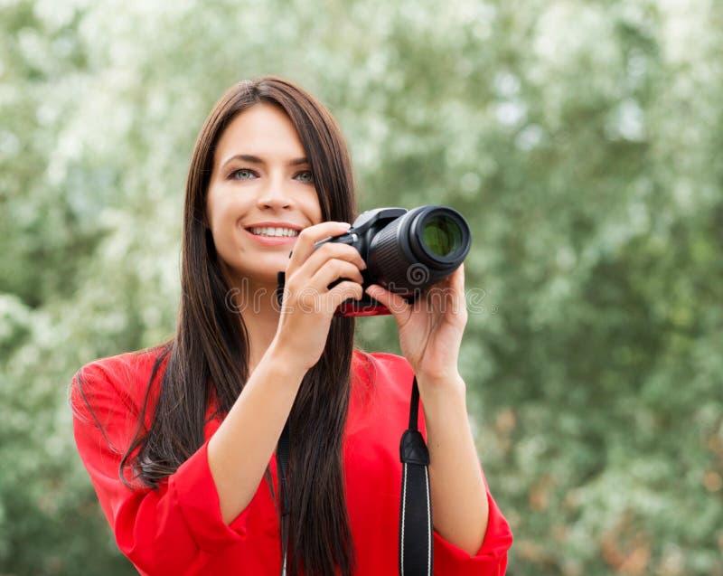 Junger schöner Brunette, der mit neuer slr Fotokamera glücklich ist lizenzfreie stockbilder