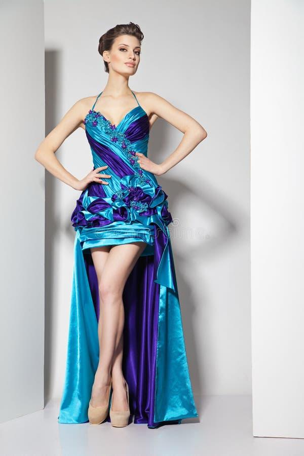 Junger schöner Brunette im blauen Kleid auf Weiß stockfotos