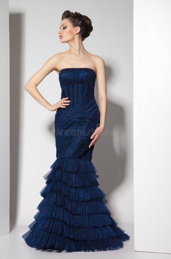 Junger schöner Brunette im dunkelblauen Kleid an lizenzfreie stockfotografie