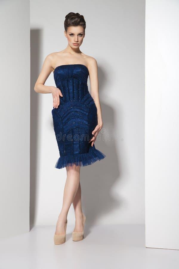 Junger schöner Brunette im dunkelblauen Kleid an lizenzfreie stockbilder