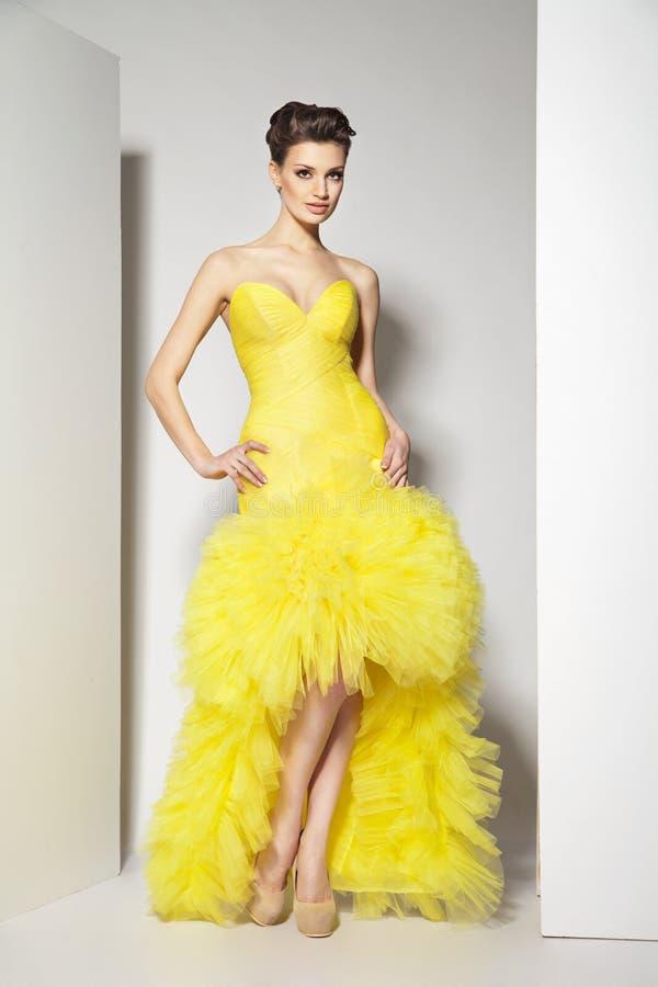 Junger schöner Brunette im gelben Kleid auf Weiß stockfotografie