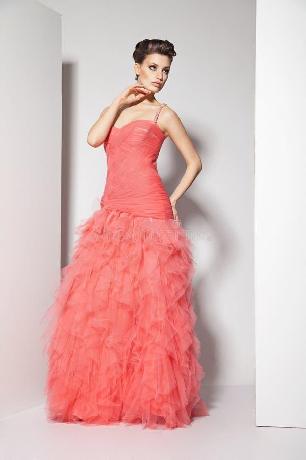 Junger schöner Brunette im roten Kleid auf Weiß stockbilder