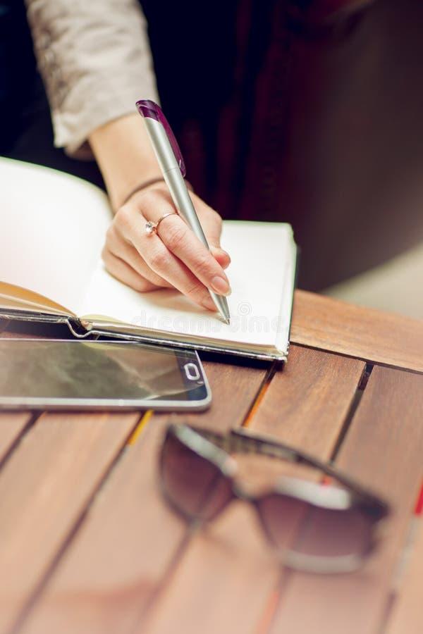 Junger schöner Geschäftsfraubehälter auf einem Notizblock, Abschluss oben auf ihrer Hand, arbeitend im downtow lizenzfreies stockbild