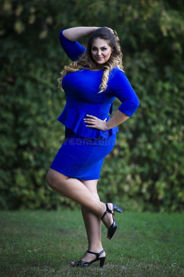 Junger schöner Kaukasier plus Größenmodell im blauen Kleid draußen, xxl Frau auf Natur lizenzfreies stockbild