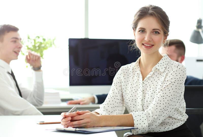 Junger schöner lächelnder Sekretär im Büro, das in camera schaut stockbilder