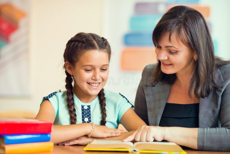 Junger schöner Lehrer mit Schulmädchenschule stockbilder