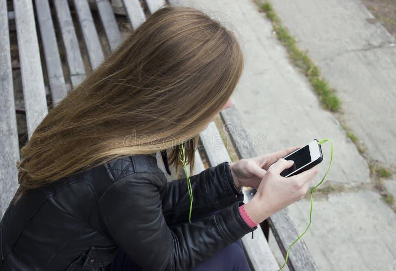 Junger schöner Mädchenblick und hörende Musik an Ihrem Handy auf den alten Stadien setzt auf die Bank stockfotos