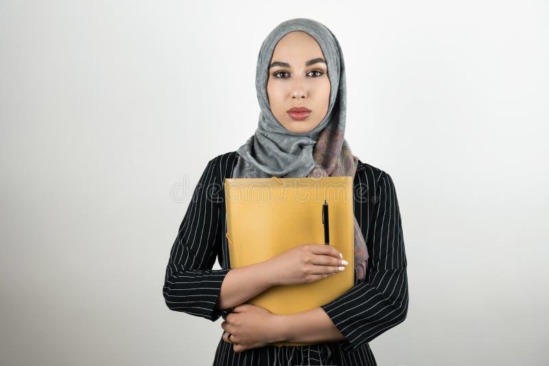 Junger schöner moslemischer Kopftuch-Holdingordner hijab Turban der Geschäftsfrau tragender mit Dokumenten und Stift lokalisiert lizenzfreie stockbilder