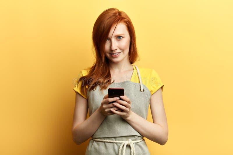 Junger schöner rothaariger Gärtner mit dem Schutzblech, das eine Mitteilung mit dem Mobile sendet stockfotos