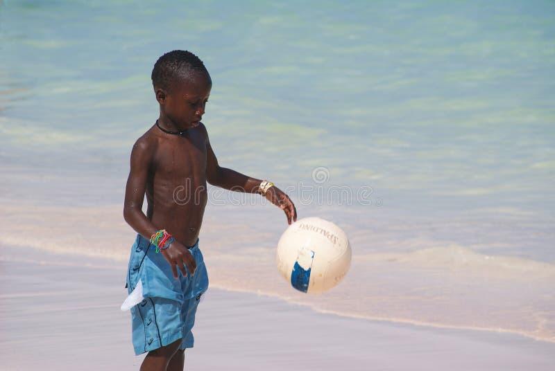 Junger schöner schwarzer Junge in den blauen kurzen Hosen, die Fußball auf dem sonnigen karibischen Strand gleich nach Schwimme lizenzfreies stockbild