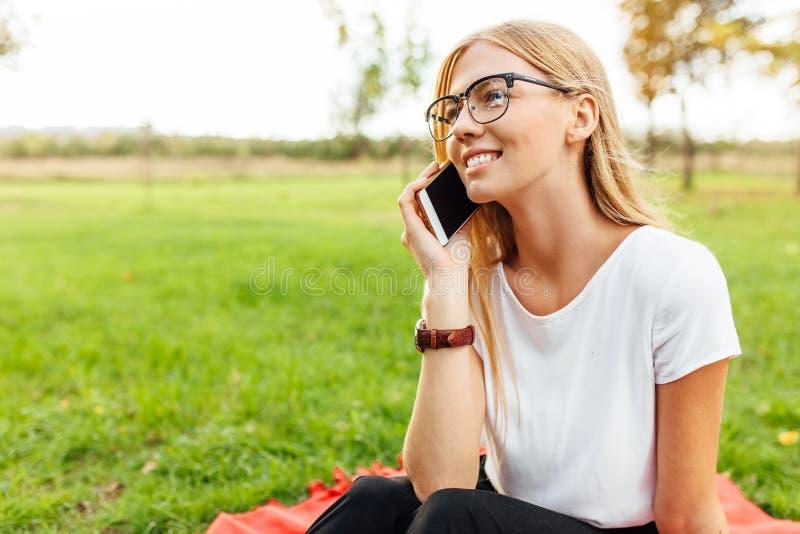 Junger schöner Student mit den Gläsern, sprechend am Telefon und stockfoto