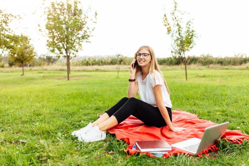 Junger schöner Student mit den Gläsern, sprechend am Telefon und lizenzfreie stockfotos