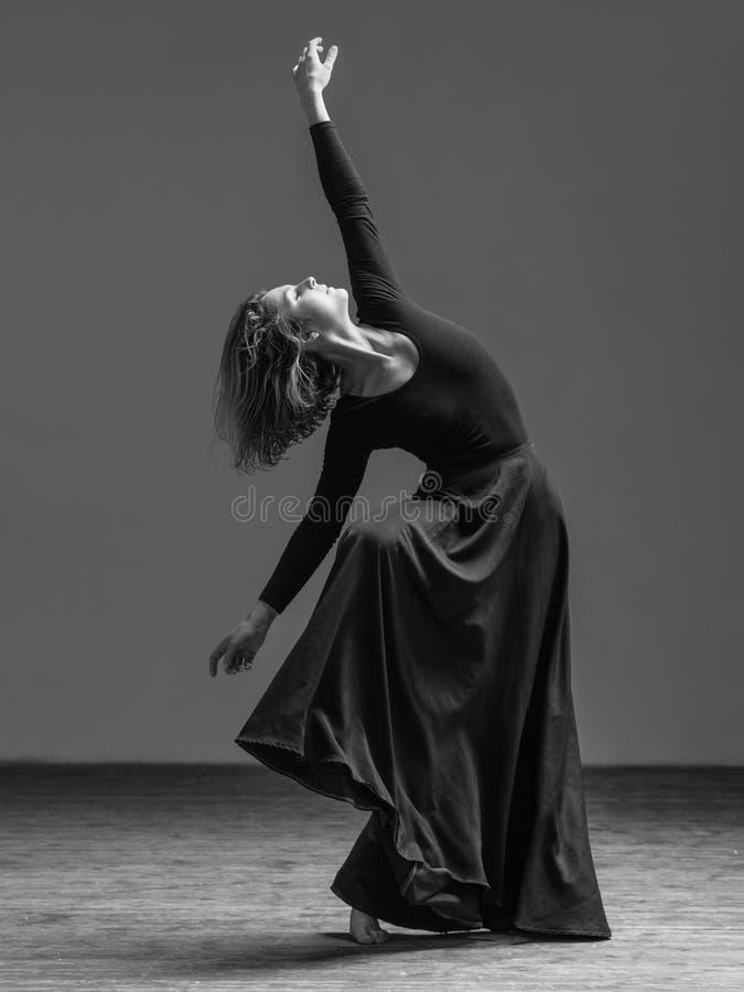 Junger schöner Tänzer, der im Studio aufwirft stockfotos
