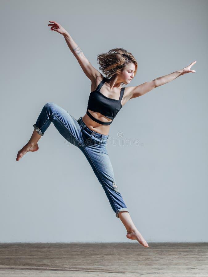 Junger schöner Tänzer, der im Studio aufwirft lizenzfreie stockbilder
