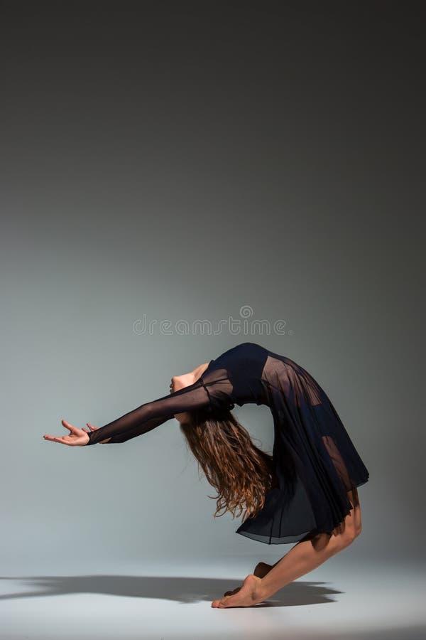 Junger schöner Tänzer im schwarzen Kleid, das auf einem dunkelgrauen Studiohintergrund aufwirft stockfotografie