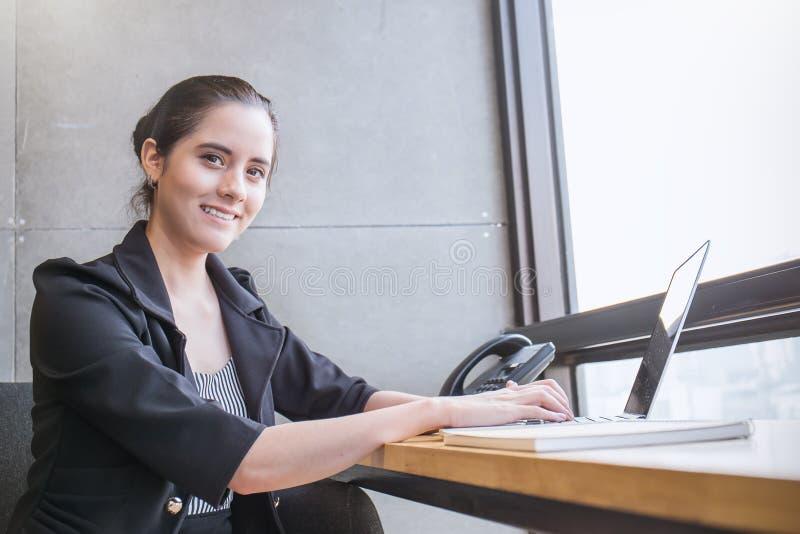 Junger schöner tragender Anzug der Geschäftsfrau, der auf Stuhl mit Laptop sitzt stockfoto