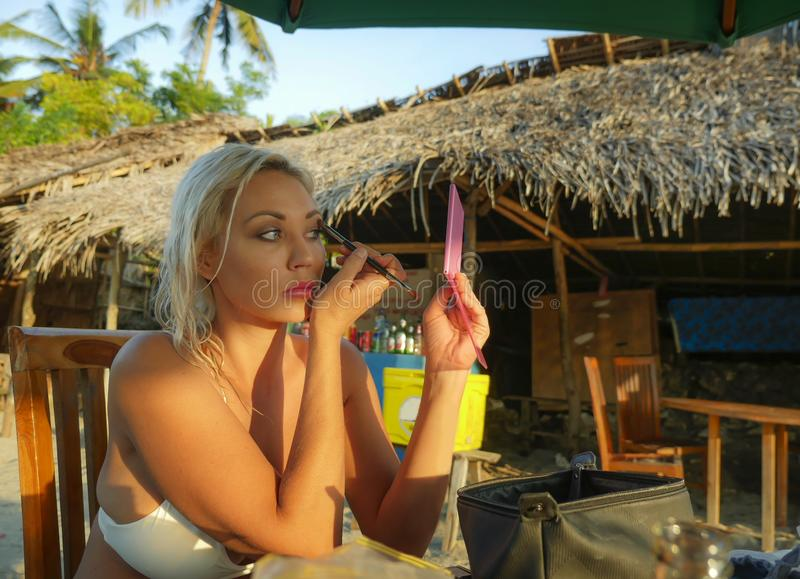 Junger schöner und entspannter blonder Frauenholdingspiegel, der das Make-up anwendet den Bürstenlidschatten sitzt am Feiertagsst lizenzfreies stockfoto