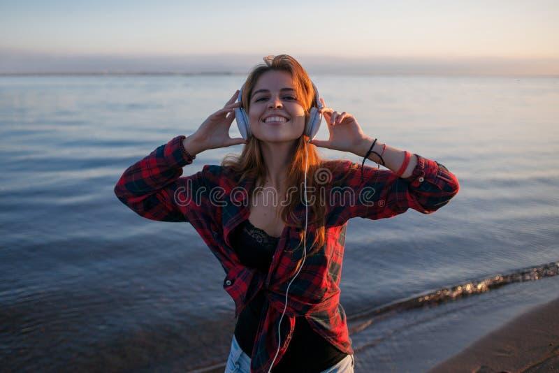 Junger schöner weiblicher Musikfan Tanzen und Hören Musik auf Kopfhörern Porträt auf dem Seehintergrund stockfoto