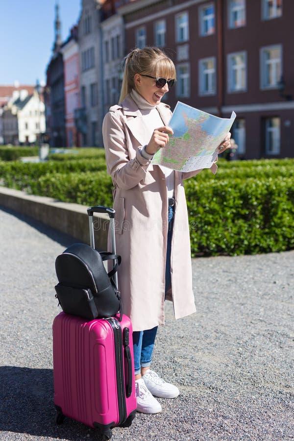 Junger schöner weiblicher Reisender mit Koffer verlor in der Stadt stockbilder