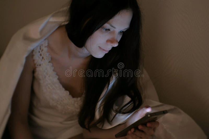 Junger Schönheit Brunette betrachtet soziale Netzwerke in ihrem Handy im Bett, bevor er schläft und lächelt lizenzfreies stockbild