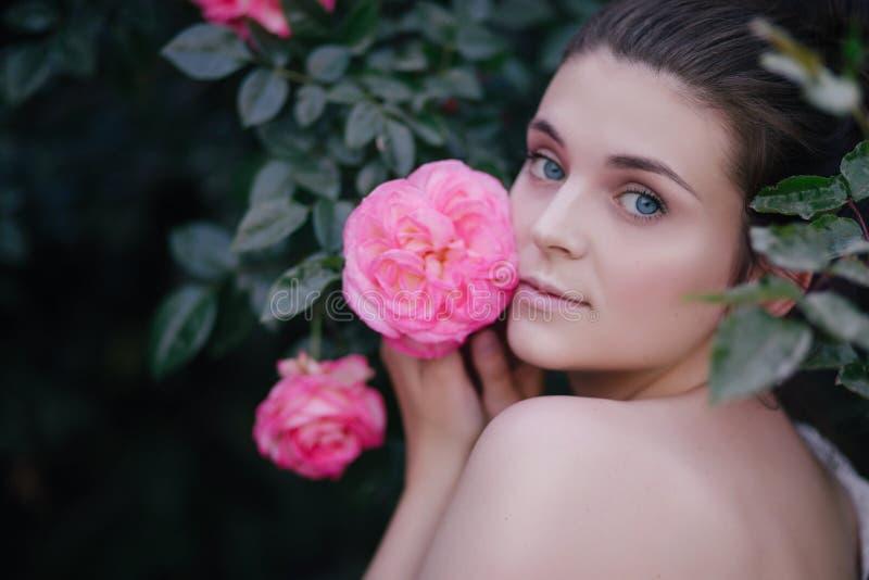 Junger Sch?nheitsportr?tabschlu? herauf die Aufstellung mit rosa Rosenblumen in einem Garten lizenzfreies stockfoto
