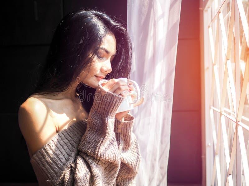 Junger Schönheitstrinkbecher Kaffee nach Hause am Fenster sitzend stockbild