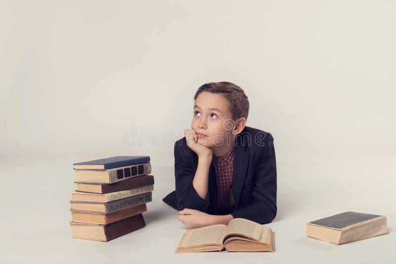 Junger Schüler, der auf einem grauen Hintergrund träumt lizenzfreies stockfoto