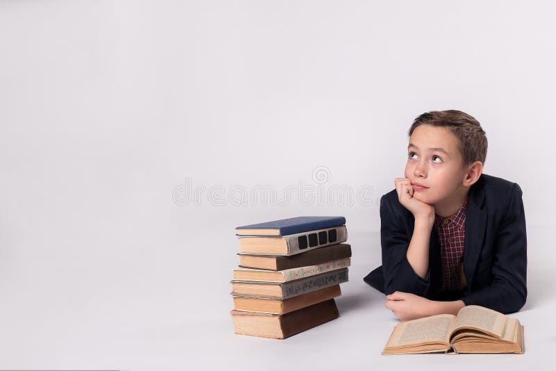 Junger Schüler, der auf einem weißen Hintergrund träumt stockbilder