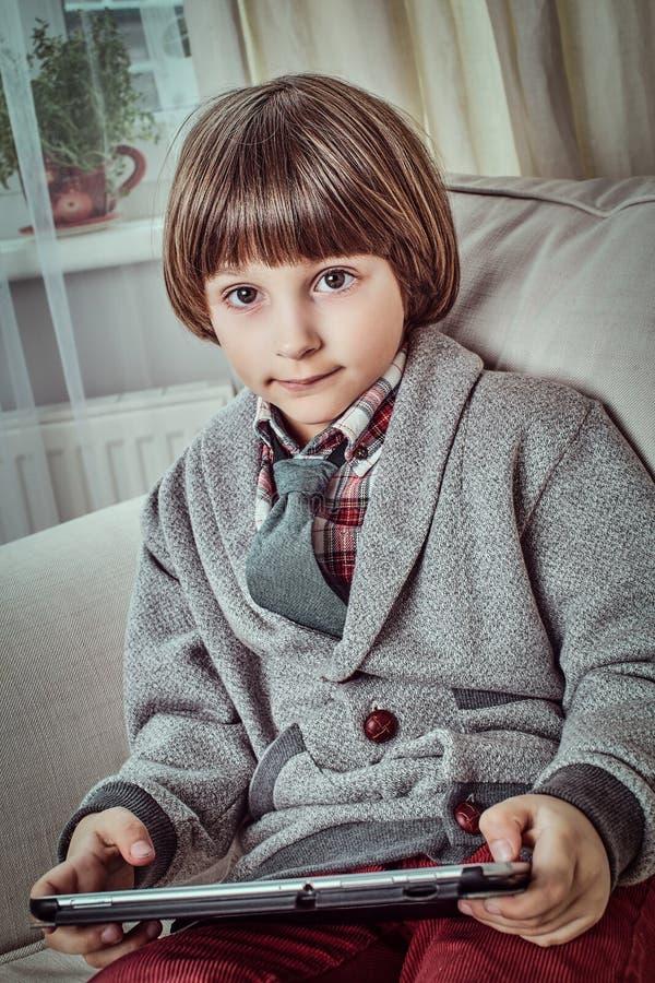 Junger Schüler, der die elegante Kleidung hält eine digitale Tablette beim auf einer Couch zu Hause sitzen trägt lizenzfreie stockbilder