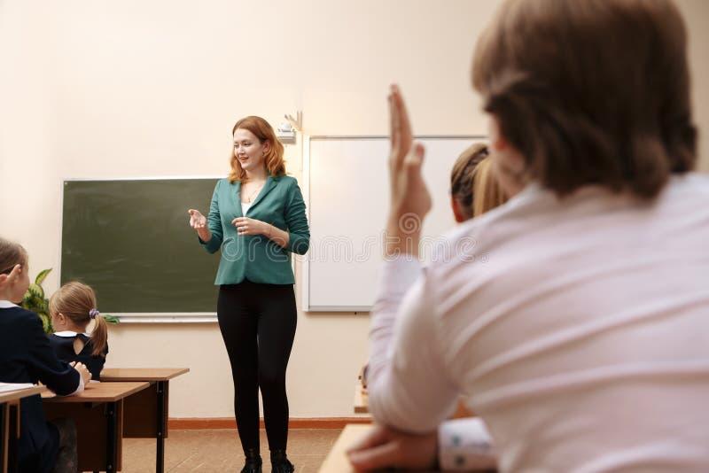 Junger Schüler, der herauf seine Hand in Klasse sich setzt, um eine Frage für seinen Lehrer zu beantworten, Ansicht von hinten se lizenzfreie stockfotos