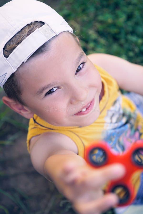 Junger Schüler, der populäres Unruhespinnerspielzeug - nahes hohes Porträt hält Glückliches lächelndes Kind, das mit Spinner spie stockbilder