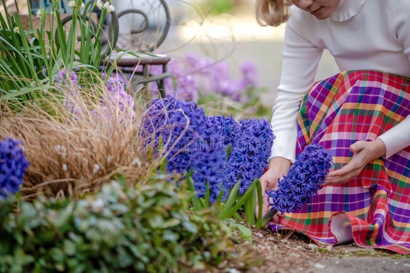 Junger sch?ner Asiating?rtner um ihrer Blume im Hinterhof sich k?mmern lizenzfreie stockfotos