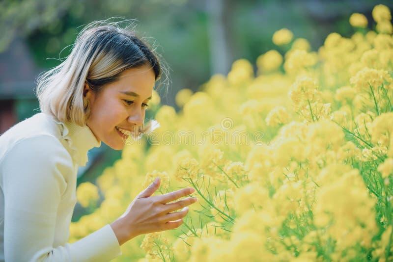 Junger sch?ner Asiating?rtner um ihrer Blume im Hinterhof sich k?mmern Gelbe Blume im Freien stockfotos