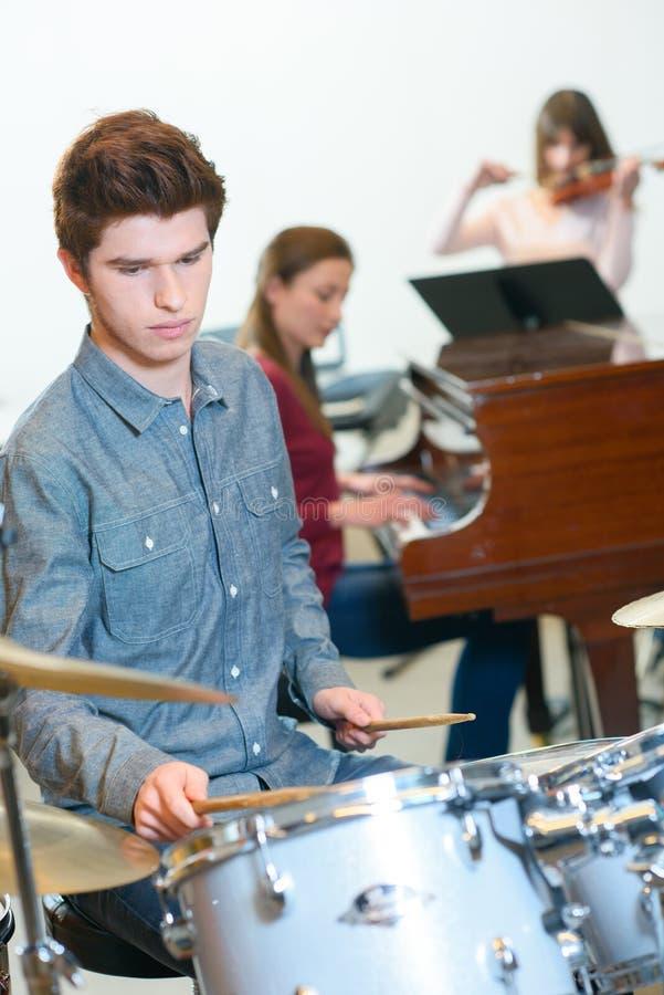 Junger Schlagzeuger mit Trommelstöcken in der Musikklasse lizenzfreies stockfoto