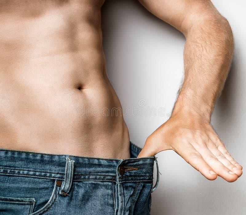 Junger schlanker Mann ist mit seinem Körper-Diät-gesunden Lebensmittel-Konzept zufrieden stockbild