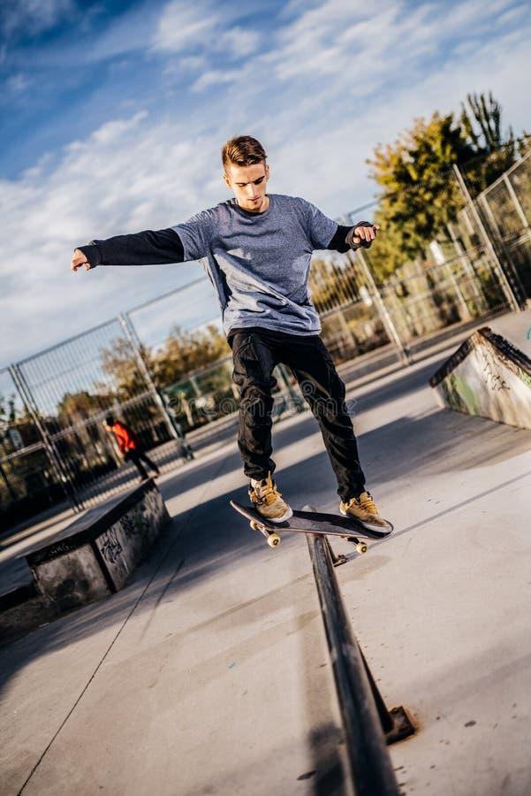 Junger Schlittschuhläufer, der ein Schleifen auf Skatepark während des Sonnenuntergangs macht lizenzfreie stockbilder