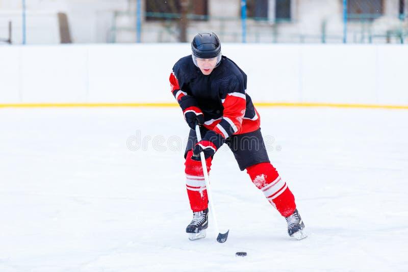 Junger Schlittschuhläufermann im Angriff Eishockeyspiel lizenzfreie stockbilder