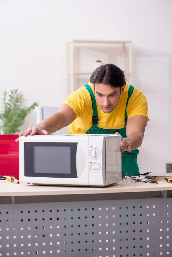 Junger Schlosser, der im Einsatz Mitte der Mikrowelle repariert stockfotos