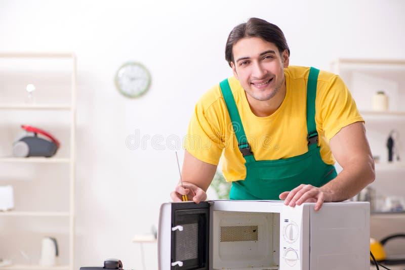 Junger Schlosser, der im Einsatz Mitte der Mikrowelle repariert lizenzfreie stockfotografie