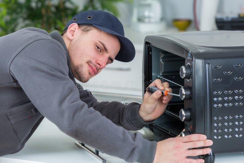 Junger Schlosser, der Ofen mit Schraubenzieher in der Kundenküche repariert stockbilder