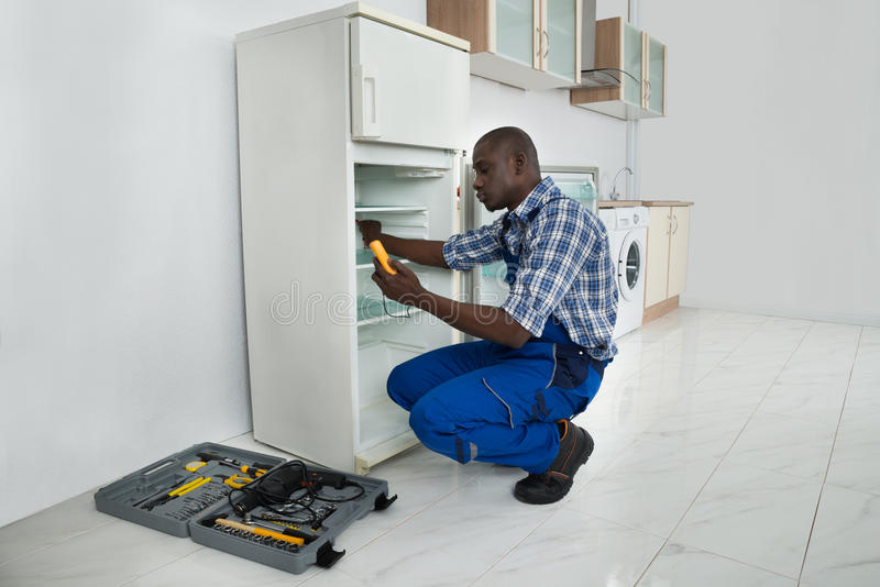Junger Schlosser Repairing Refrigerator stockfotos