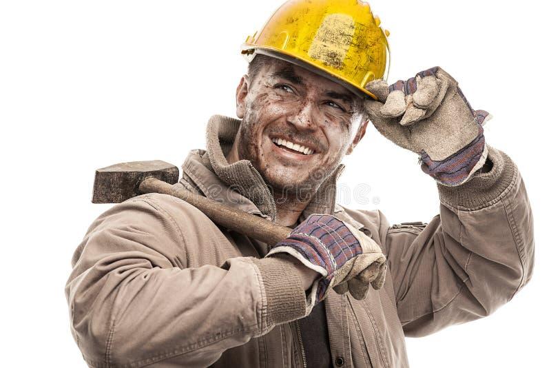 Junger schmutziger Arbeitskraft-Mann mit dem Schutzhelmsturzhelm, der einen Hammer a hält lizenzfreie stockfotografie