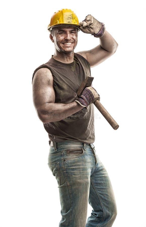 Junger schmutziger Arbeitskraft-Mann mit dem Schutzhelmsturzhelm, der einen Hammer a hält lizenzfreies stockfoto