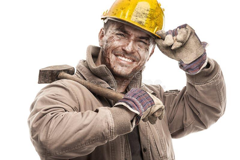 Junger schmutziger Arbeitskraft-Mann mit dem Schutzhelmsturzhelm, der einen Hammer a hält lizenzfreie stockfotos
