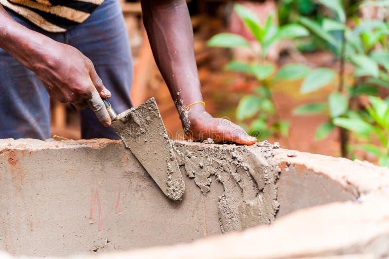 Junger Schwarzafrikanerjunge übergibt Gebäude waterwell mit Spachtel und Zement stockfoto